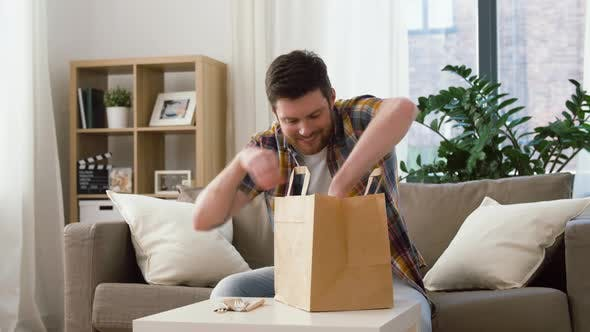 Thumbnail for Smiling Man Unpacking Takeaway Food at Home