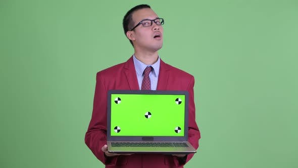 Thumbnail for Happy Asian Businessman Thinking While Showing Laptop