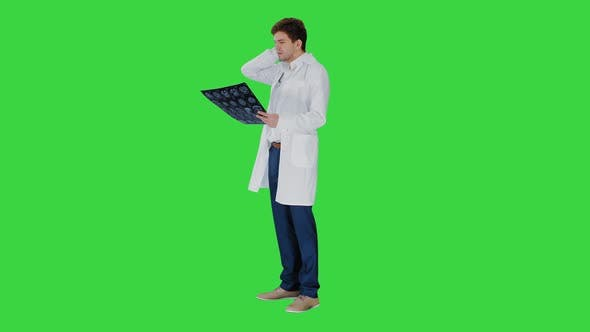 Frustrated Male Doctor Examining Computed Tomography Scan of Brain on a Green Screen, Chroma Key.