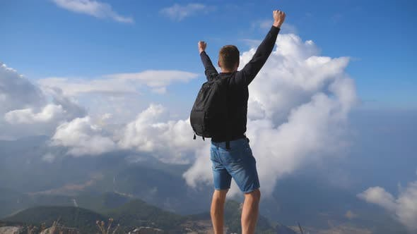 Thumbnail for Young Male Hiker Reaching Up Top of Mountain and Raising Arms. Man Enjoying Freedom During Summer