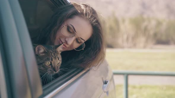 Thumbnail for Happy Girl with Cute Cat Sits in Auto Against Meadow
