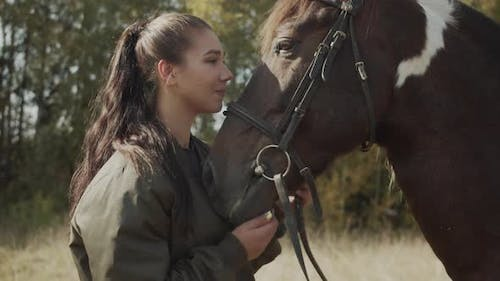 A Charming Young Woman Expresses Her Gratitude To a Horse for a Pleasant Ride on It By Hugging