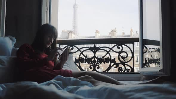 Thumbnail for Happy Attractive Tourist Woman Smiling, Relaxing on Bed at Open French Balcony in Paris Using