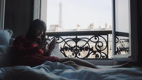 Thumbnail for Glückliche Attraktive Tourist Frau lächelnd, Entspannen auf dem Bett auf Offenen Französisch Balkon in Paris mit