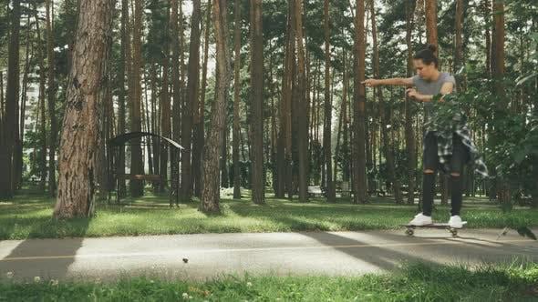 Thumbnail for Happy girl skateboarding in park. Woman skateboarding.