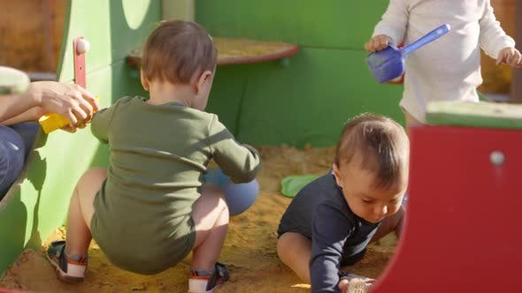 Three Toddlers Playing Outdoors in Sand Pit