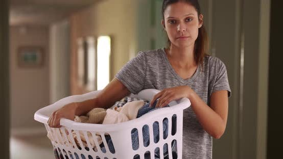 Thumbnail for Pretty Caucasian woman at home holding basket of clean clothes