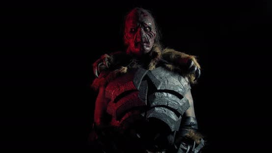 Orc in Metal Armor Is Standing in Dark Red Lighting and Lifting Up a Sword,
