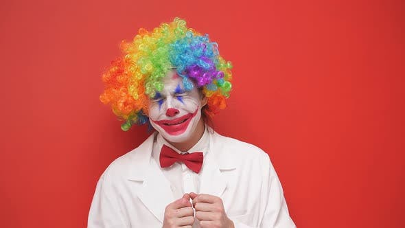 A Clown Smiling with a Happy Face Dressed in a White Outfit and a Bow Tie with a Painted Face on an