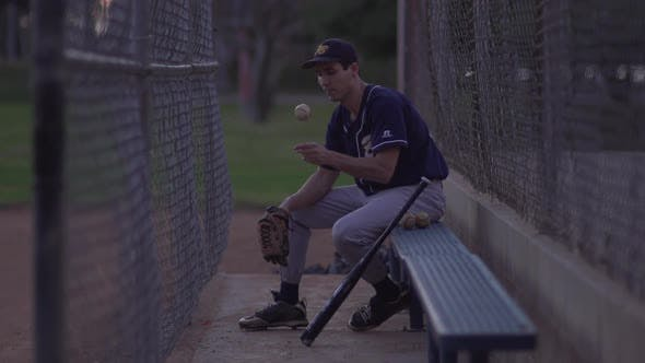 A baseball player resting on the bench.