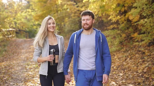 Happy Young Couple Strolling Through the Woods Contemplating the Beauty of Autumn Nature After a Run