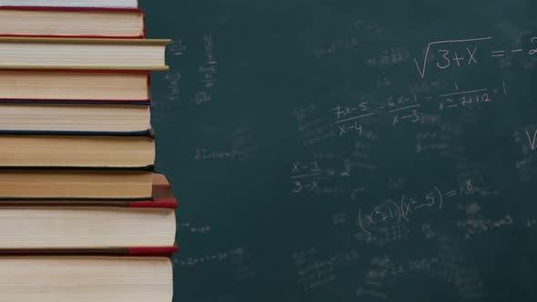 Stapel von Büchern gegen mathematische Gleichungen auf Black Board