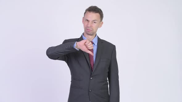 Cover Image for Studio Shot of Angry Businessman Giving Thumbs Down