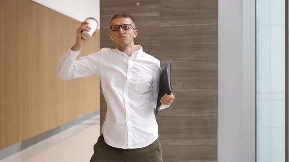 Thumbnail for Funny Businessman With Coffee Cup Dancing In Wireless Airpods In Office Hall