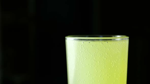 Thumbnail for Half of Full Glass with Carbonated Yellow Drink on a Black Background