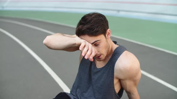 Thumbnail for Close Up of Tired Runner Sitting on Track After Running Workout