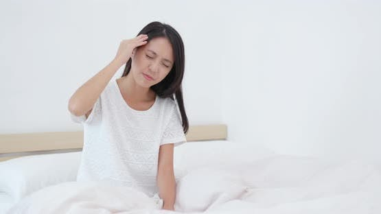 Woman feeling back pain and tired on bed