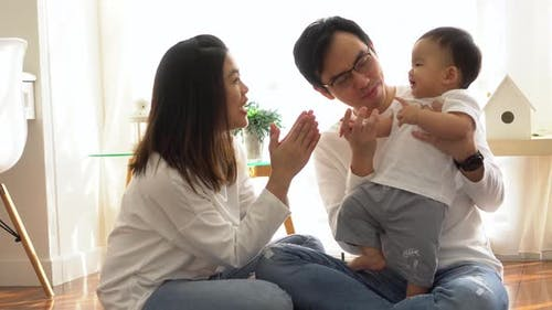 Happy Asian Family Playing Games and Clapping Hands with Baby Boy at Home