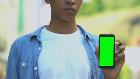Thumbnail for Serious black male teenager pointing finger into smartphone