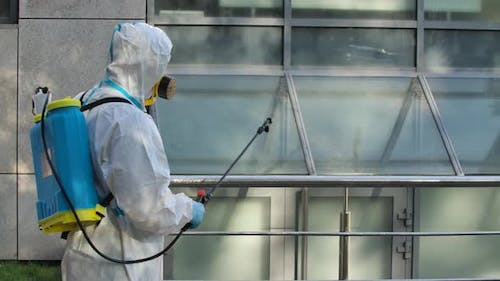 Worker in a Protective Suit and a Respirator Disinfects, Sprays Chemicals on the Surface of the