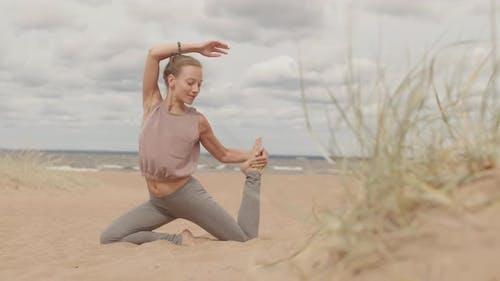 Young Woman Doing Yoga Asana on Beach