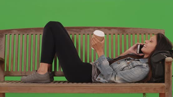 Thumbnail for Cute girl lying down on bench talking on cellphone in front green screen wall