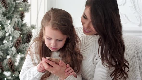 Thumbnail for Young Mother Teaching Her Daughter How To Use Smartphone in Christmas Decorated Room