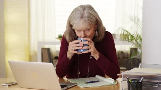 Thumbnail for Mature woman drinking coffee using laptop computer