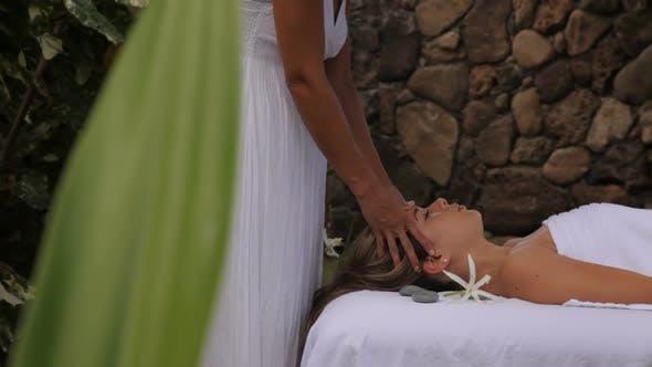 Thumbnail for Woman gets massage at tropical resort spa