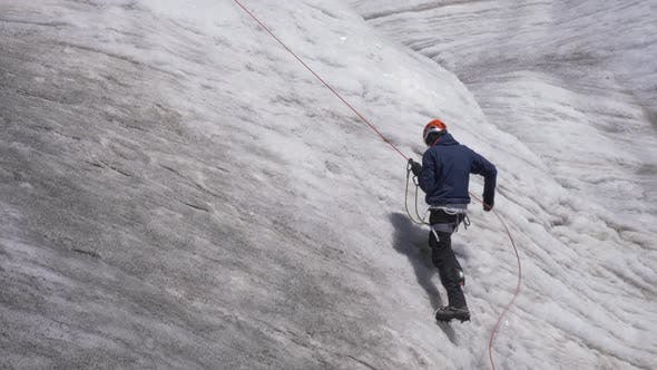 Thumbnail for Mountaineer Man in Crampons Is Using Jumar on Fixed Rope To Ascend on Steep Snowy Slope