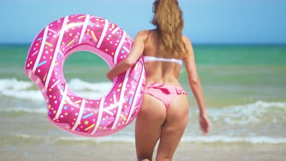 Happy Young Woman, with Sunglasses and Swim Toy, Pink Donut, To Run Water on Beach. Playful Woman