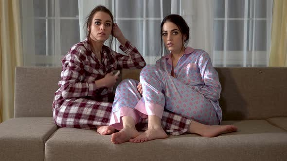Thumbnail for Twin Sisters in Pajamas Are Sitting on the Sofa and Choosing What To Watch on TV in the Living Room
