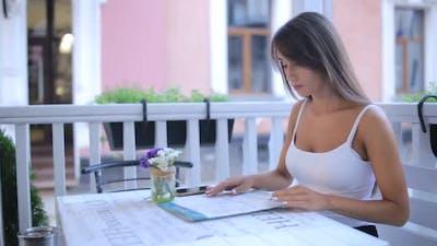 Beautiful Woman Looking at Menu in Restaurant