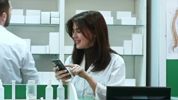 Thumbnail for Young Female Pharmacist Texting Messages Using Mobile Phone, Smiling and Talking To Her Male