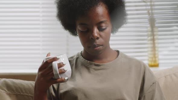 Afroamerikanische Frau trinkt Tee und benutzt Laptop zu Hause