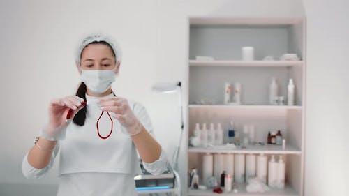 A Nurse Holding a Tourniquet Before Pulling Blood