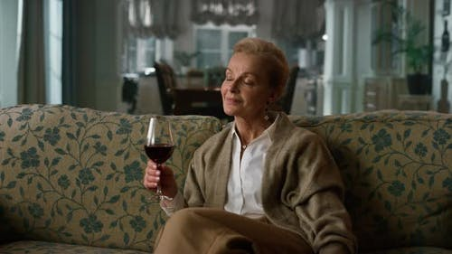 Dreamy Mature Woman Tasting Red Wine Glass in Vintage Living Room