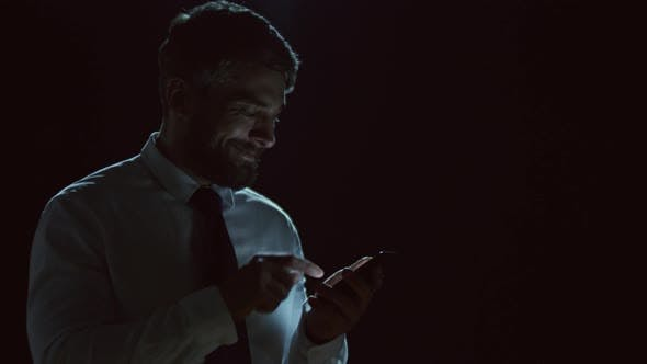 Thumbnail for Businessman Using Smartphone in the Darkness