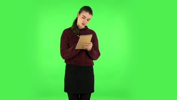 Thumbnail for Girl Stands and Thinks, Then Angrily Writes with Pencil in Notebook. Green Screen