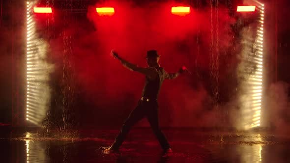 Thumbnail for A Man Is Silhouetted with Glowing Grenade in a Dark Smoky Studio. A Stylish Entertainer Performs a