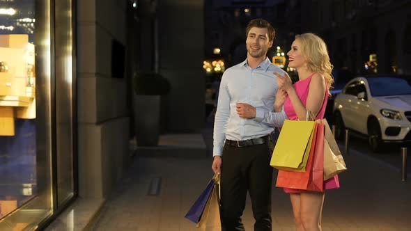 Thumbnail for Couple of Shopaholics Walking Along Shopping Street Looking at Discount and Sale