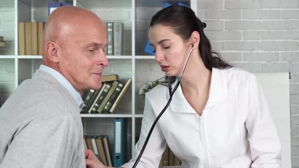 Female Doctor Use Stethoscope To Listen Heart of Elderly Man Patient