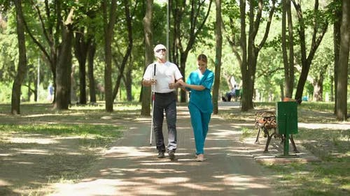 Young Nurse Holding Blind Old Patient Walking in Park, Vision Restore Clinic