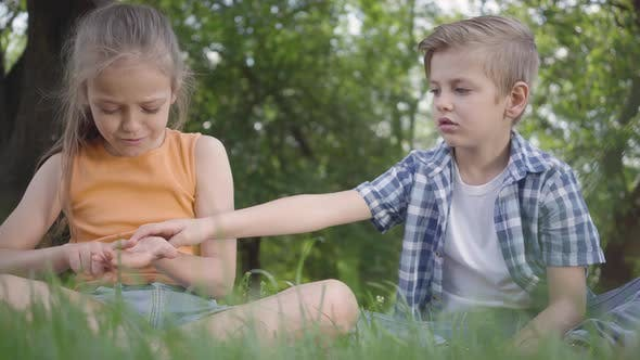 Thumbnail for Two Funny Kids Sitting on the Grass in the Park Playing. The Boy Takes Ladybug From Girl's Hand. A