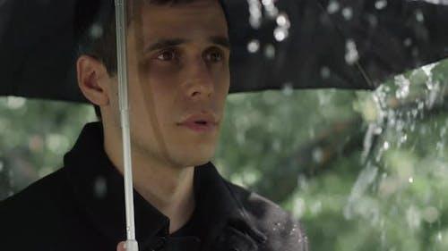 Mann unter Schirm bei der Beerdigung