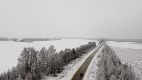Aerial View of a Cars Driving in a Foggy and Snowy Day