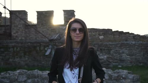 Gorgeous Brunette with Sunglasses Smiling and Posing Against Medieval Stronghold in the Background