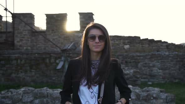 Thumbnail for Gorgeous Brunette with Sunglasses Smiling and Posing Against Medieval Stronghold in the Background
