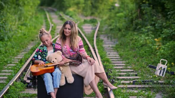 Thumbnail for Happy Traveling Mom and Daughter Sitting on Travel Suitcase and Singing Song on Railway. Traveling