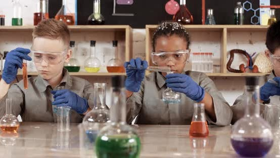 Laboratory Experience in a Chemistry Lesson, Kids in Protective Glasses Pours a Liquids Into a